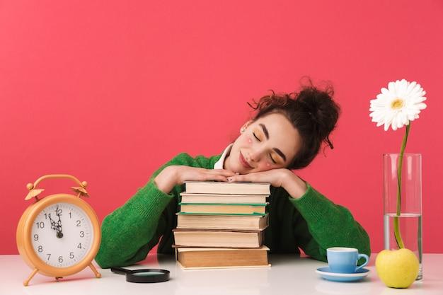 Красивая молодая девушка студента, сидящая за изолированным столом, учится с книгами, спит