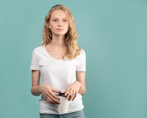 Красивая молодая девушка студента с чашкой кофе на стене нейтрального тона цвета голубой.