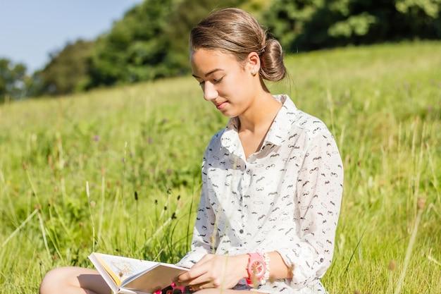 공원에서 책을 읽는 아름다운 젊은 학생