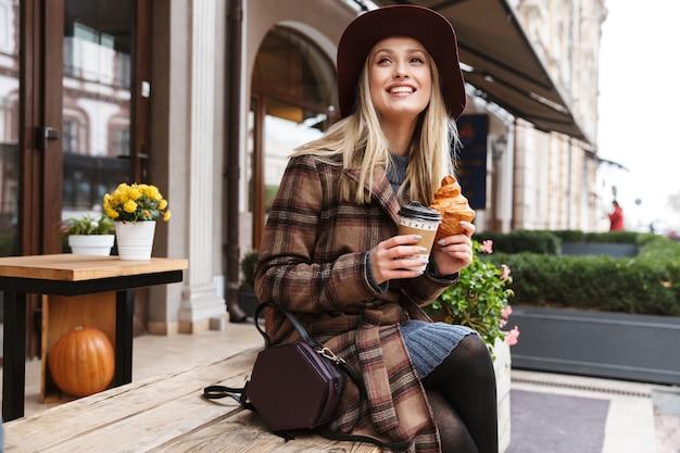 Красивая молодая стильная блондинка в пальто сидит на открытом воздухе, ест круассан, пьет кофе