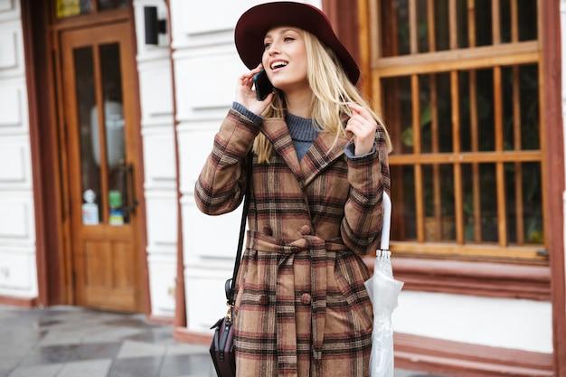 야외에서 걷는 코트를 입고 아름다운 젊은 세련된 금발의 여자, 휴대 전화에 대 한 얘기