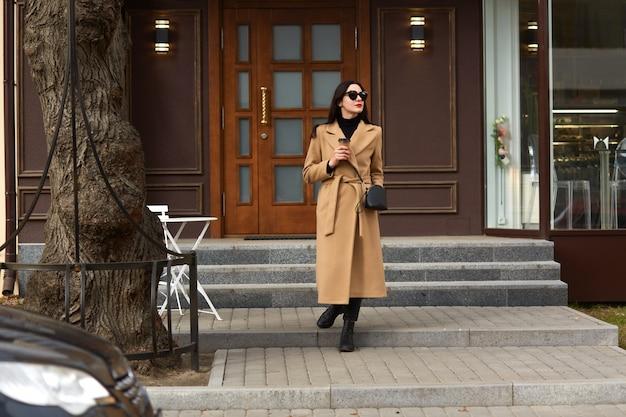 長いベージュのコート、黒いシャツと靴を身に着けている美しい若いスタイリッシュなブルネットの女性は、街の通り、トレンディなカジュアルな服装とサングラスで魅力的な女性を歩いて、テイクアウトのコーヒーを飲みます。