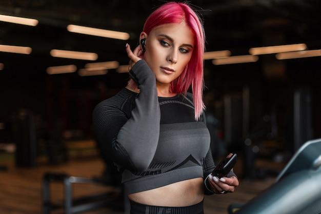 Красивая молодая стильная девушка с макияжем и розовыми волосами надевает беспроводные наушники и начинает бегать на беговой дорожке в тренажерном зале