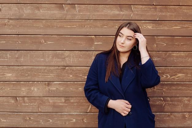 Bella giovane ragazza alla moda in parete di legno