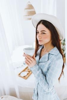 Красивая молодая стильная женщина в деловом костюме и белой шляпе, стоя возле кровати и пьет кофе в солнечное утро