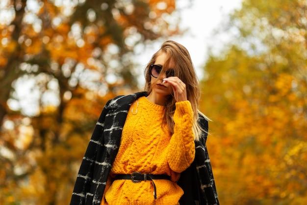 차에 앉아 유행 옷에 안경에 아름 다운 젊은 세련 된 여자. 자동차로 여행하는 모델 소녀