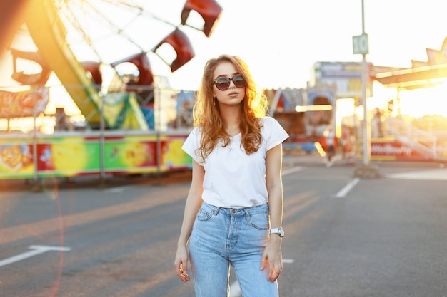 日没時に遊園地を歩くサングラスの美しい若いスタイリッシュな女性