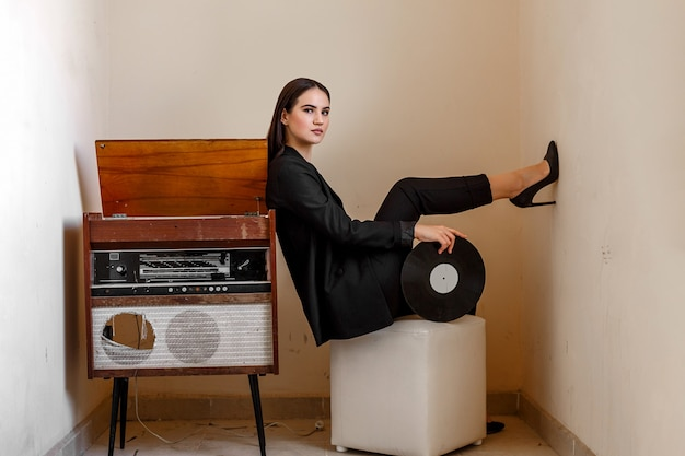 A beautiful young stylish woman near a vintage record player