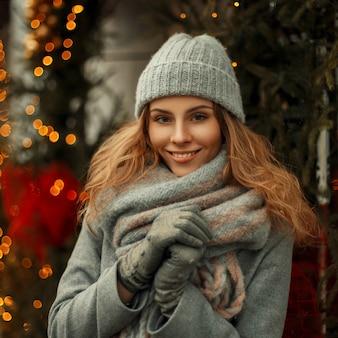 冬の日のお祝いの光を背景に通りのトレンディな灰色のコートでスカーフとファッショナブルなニット帽で笑っている美しい若いスタイリッシュな女性