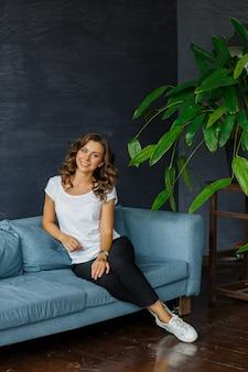 Красивая молодая стильная женщина улыбается, сидя на диване, позирует на камеру в помещении на темно-сером фоне