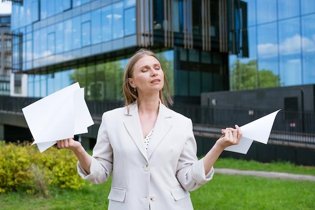 종이 문서를 들고 고전적인 도시 사무실 건물에서 산책하는 아름 다운 젊은 교외 비즈니스 여자.