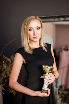 Beautiful young successful blonde woman with gold cup