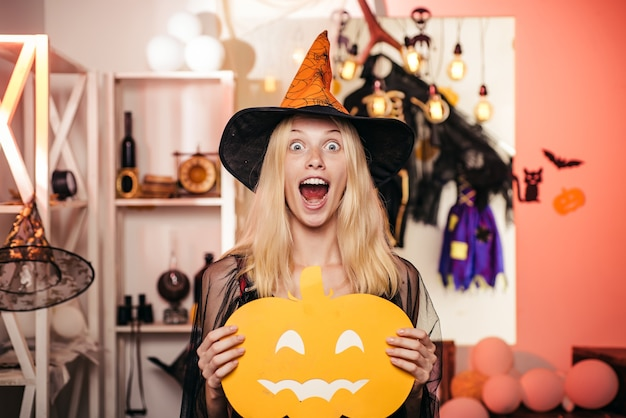 Beautiful young surprised woman in witches hat and costume holding pumpkin. pumpkin head jack lantern. trick or treat. pretty young blond witch flying on the broom, isolated against orange background.