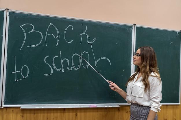 美しい若い先生は黒板に学校に戻って碑文を指しています。教育の概念