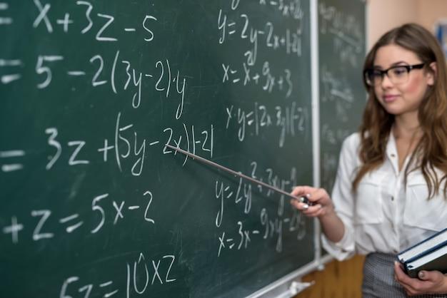 美しい若い先生は、教室での数学の練習の解決策へのポインタを示しています。教育。学校。ジョブ。