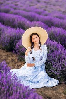 Красивый молодой предназначенный для подростков портрет девушки на открытом воздухе. брюнетка в шляпе с корзиной цветов, собирающих урожай в лавандовом поле прованс, на закате. привлекательная красивая девушка с длинными здоровыми вьющимися волосами.
