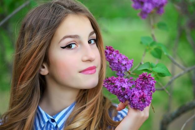 라일락 꽃에 서있는 아름 다운 젊은 십 대 소녀.