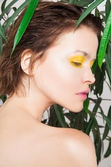 Красивая молодая девушка с идеальной кожей с свежий желтый цвет макияжа и зеленых растений. естественная красота женщины. уход за кожей лица салон красоты спа-концепция лечения