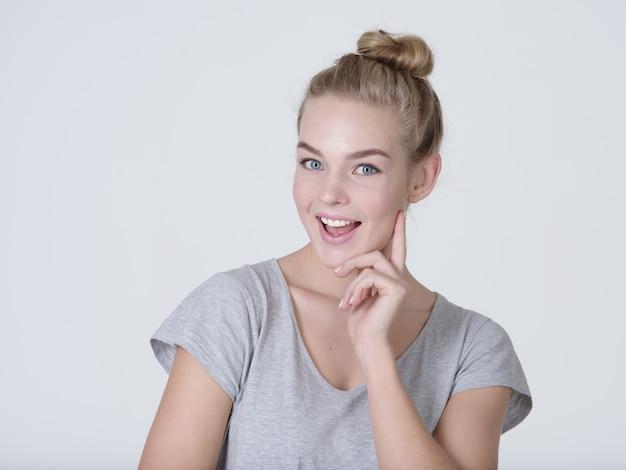 Bella giovane donna caucasica di pensiero con il dito vicino al viso isolato su sfondo bianco