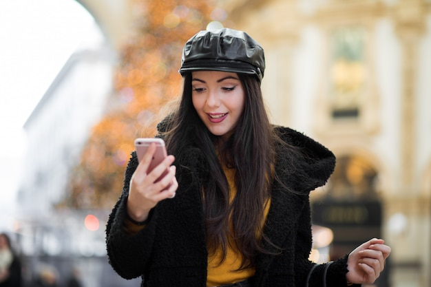 Beautiful young tourist girl in milan shopping in milan while using a smartphone