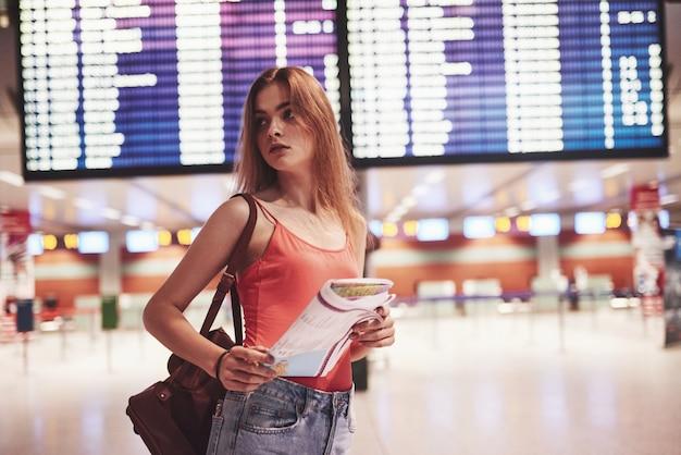 フライト情報ボードの近くの国際空港でバックパックを持つ美しい若い観光客の女の子