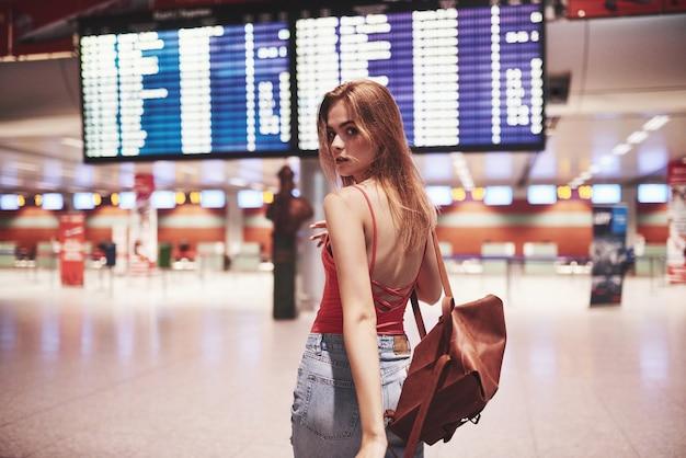 国際空港、フライト案内板の近くにバックパックを持つ美しい若い観光客の女の子。