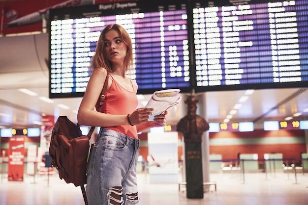 国際空港のバックパックを持つ美しい若い観光客の女の子