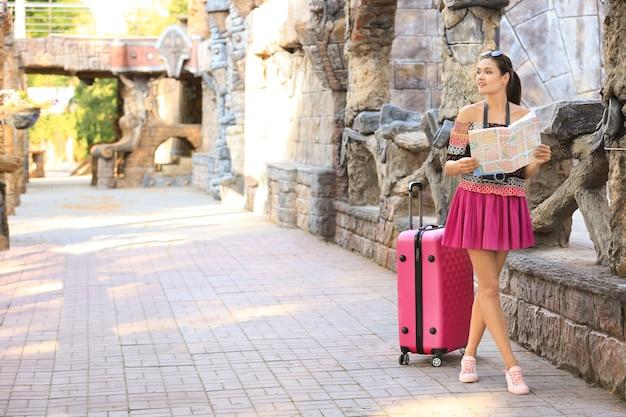 Красивый молодой турист с картой и чемоданом, стоящим возле древнего замка