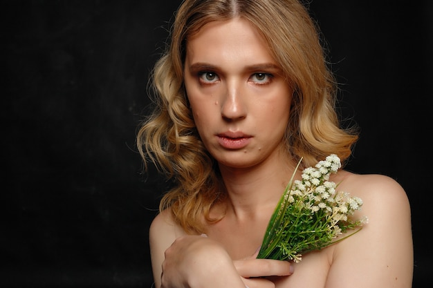 Beautiful young transgender with blond hair, dark blue, smiling, holding flowers and white cloth
