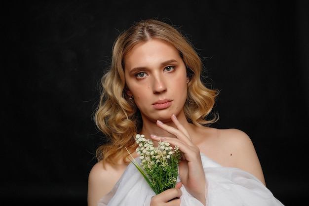 Beautiful young transgender with blond hair holding flowers