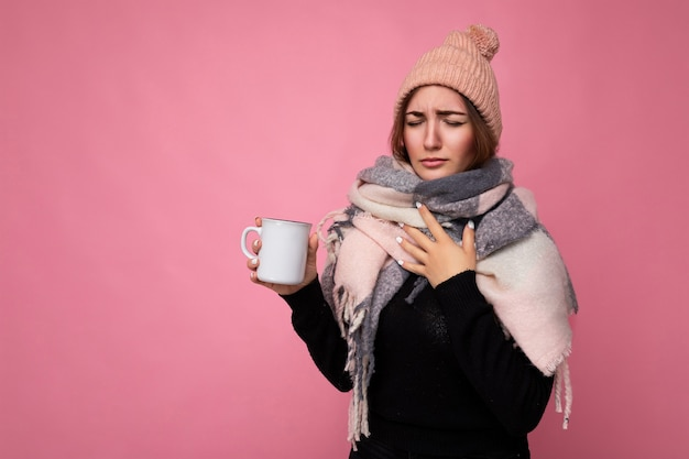 Beautiful young upset brunet woman wearing black sweater hat and warm scarf isolated over pink