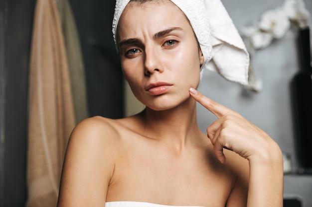 Красивая молодая расстроенная женщина, завернутая в банное полотенце, стоя в ванной комнате