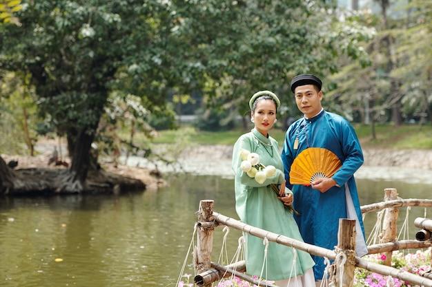 도시 연못에서 물을 바라보는 전통 의상과 모자를 쓴 아름다운 젊은 베트남 부부