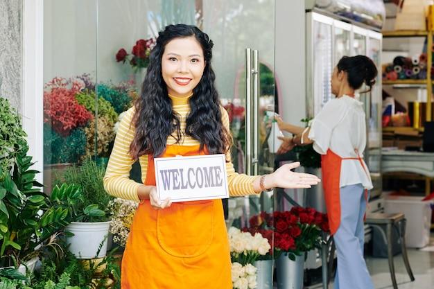 家族の花屋の入り口に立っているときにウェルカムサインを保持している美しい若いベトナム人女性