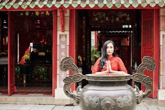 Красивая молодая вьетнамская женщина молится у медной урны с курительными палками в храме