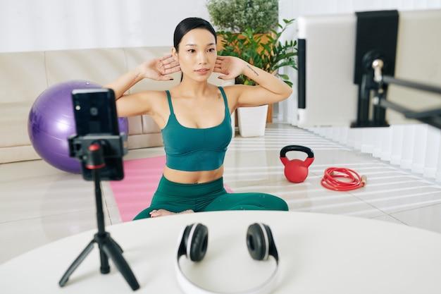 거실에서 운동하고 온라인 수업을 위해 자신을 녹음하는 아름다운 젊은 베트남 여성