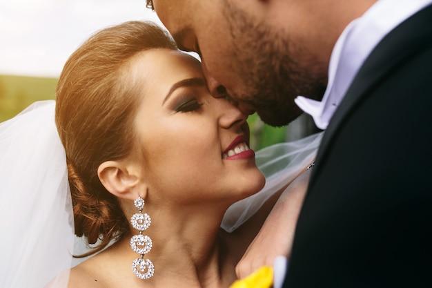 Красивая молодая свадебная пара веселится на открытом воздухе