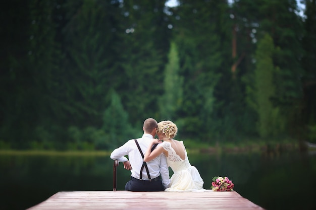 Beautiful young wedding couple sitting on the pier.