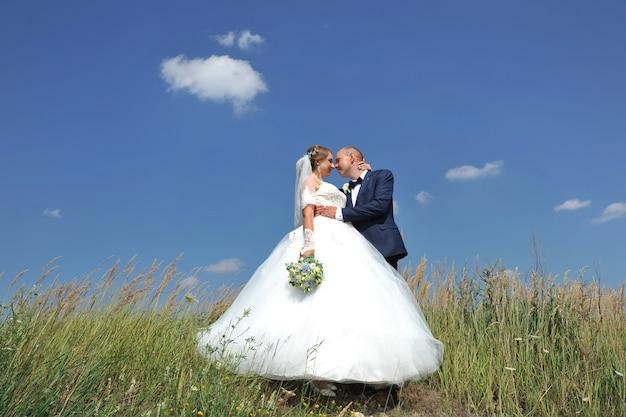 푸른 하늘과 구름의 배경에 언덕 꼭대기에 서있는 아름 다운 젊은 웨딩 커플.