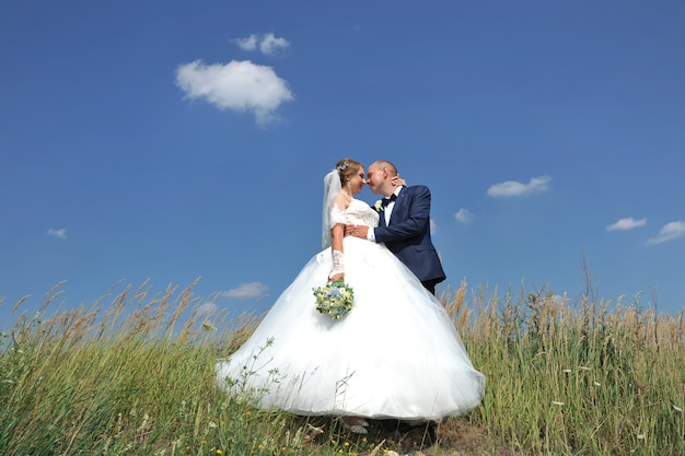 Beautiful young wedding couple standing on top of a hill on a background of blue sky and clouds.
