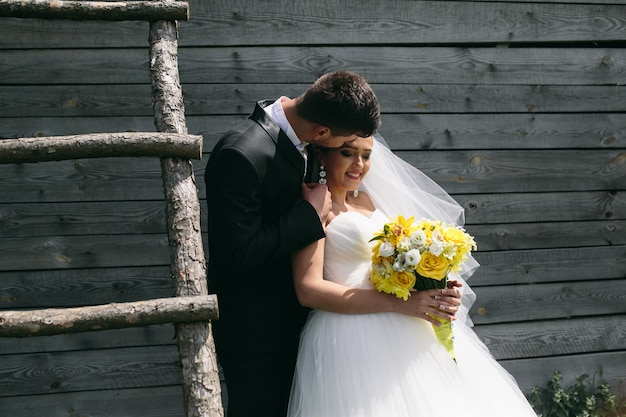 Beautiful young wedding couple stands near the old wooden house