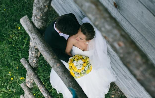 Красивая молодая свадебная пара стоит возле старого деревянного дома