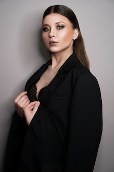 Beautiful young white girl close-up in a black jacket on a gray surface
