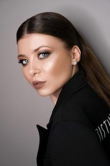 Красивая молодая белая девушка крупным планом в черной куртке на серой поверхности