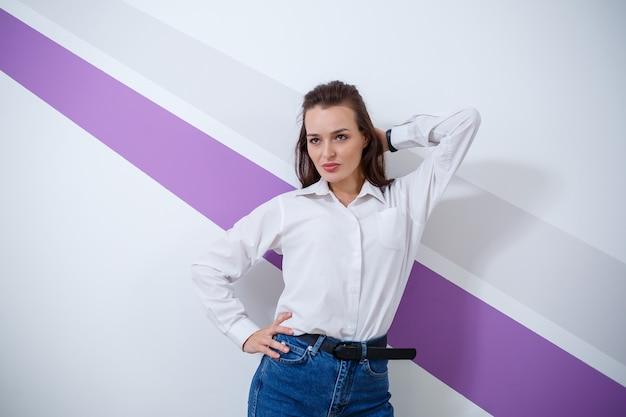 紫色の縞模様の明るい背景に白いシャツとブルージーンズに身を包んだ美しい若い白い肌の少女 Premium写真