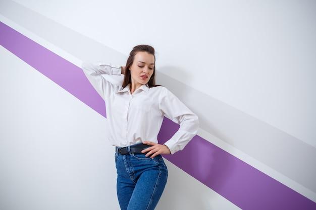 보라색 줄무늬가 있는 밝은 배경에 흰색 셔츠와 청바지를 입은 아름다운 흰색 피부 소녀