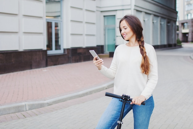 Beautiful, young, and white-toothed girl with long brown hair stopped while riding the scooter