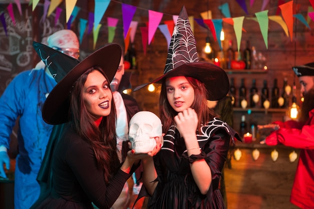 Beautiful young witches with big hats celebrating halloween. scary doctor in the background.