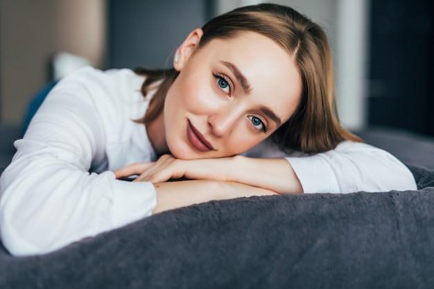 Красивая молодая женщина поправляет волосы и смотрит в камеру, лежа на кровати у себя дома