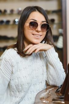 Красивая молодая женщина регулирует свои новые солнцезащитные очки, стоя в магазине оптики